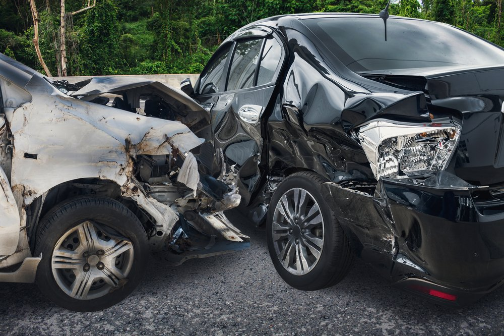 photo of two crumpled cars after a car wreck. front of light gray car smashed against drivers side of a black car