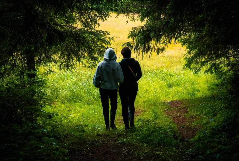 Two silhouette women go out walking from a dark forest
