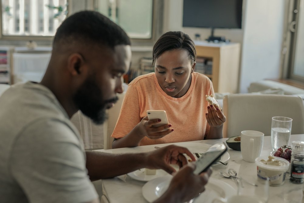 Young African American couple using their cellphones while having breakfast together at home in the morning