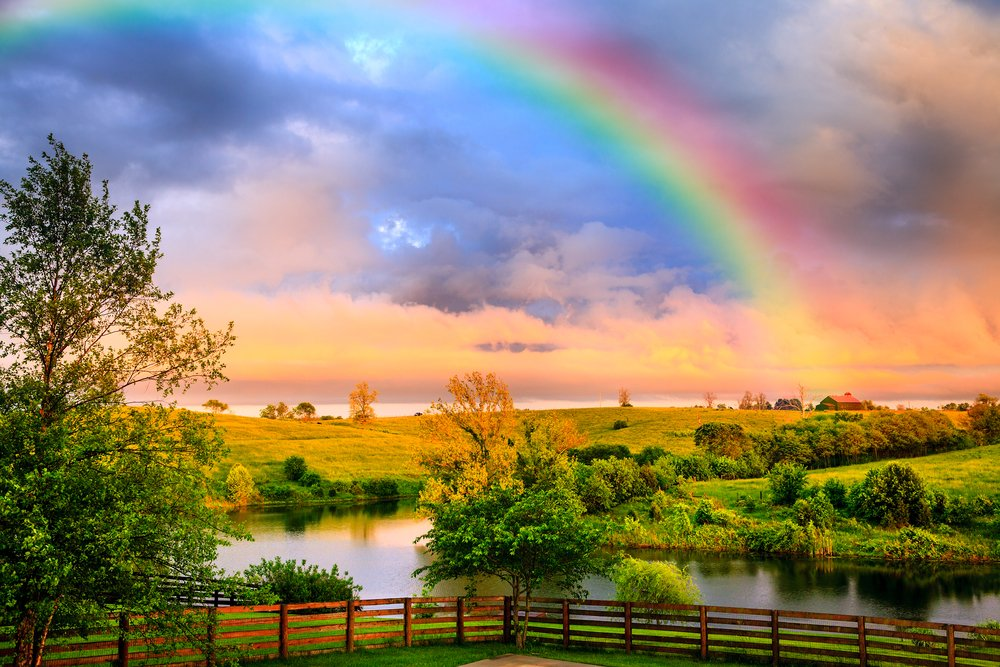 rainbow filling the sky over an idyllic countryside