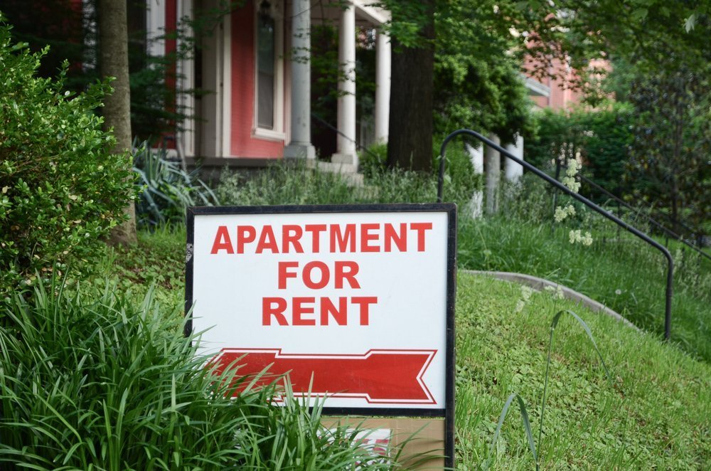 Apartment for rent sign displayed on residential street