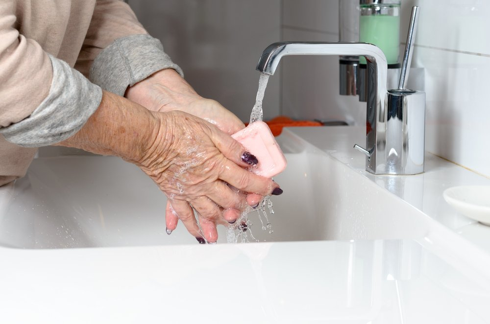 Side view of elderly woman washing hands under running tap