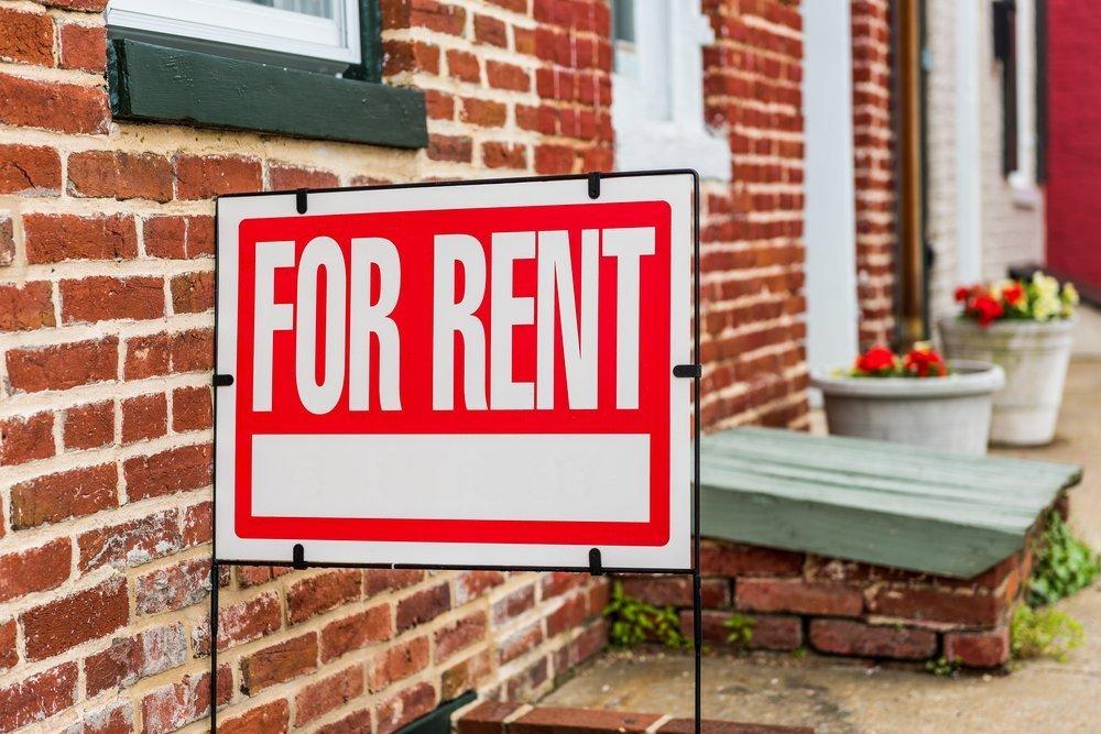 Rent sign closeup against brick building