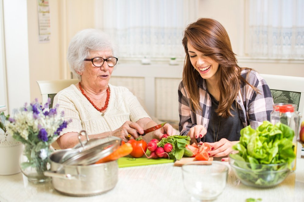 two women, one young and one elderly, cooking a meal together at home. filling the empty bedrooms of a home with roommates provides community support and income for seniors living alone