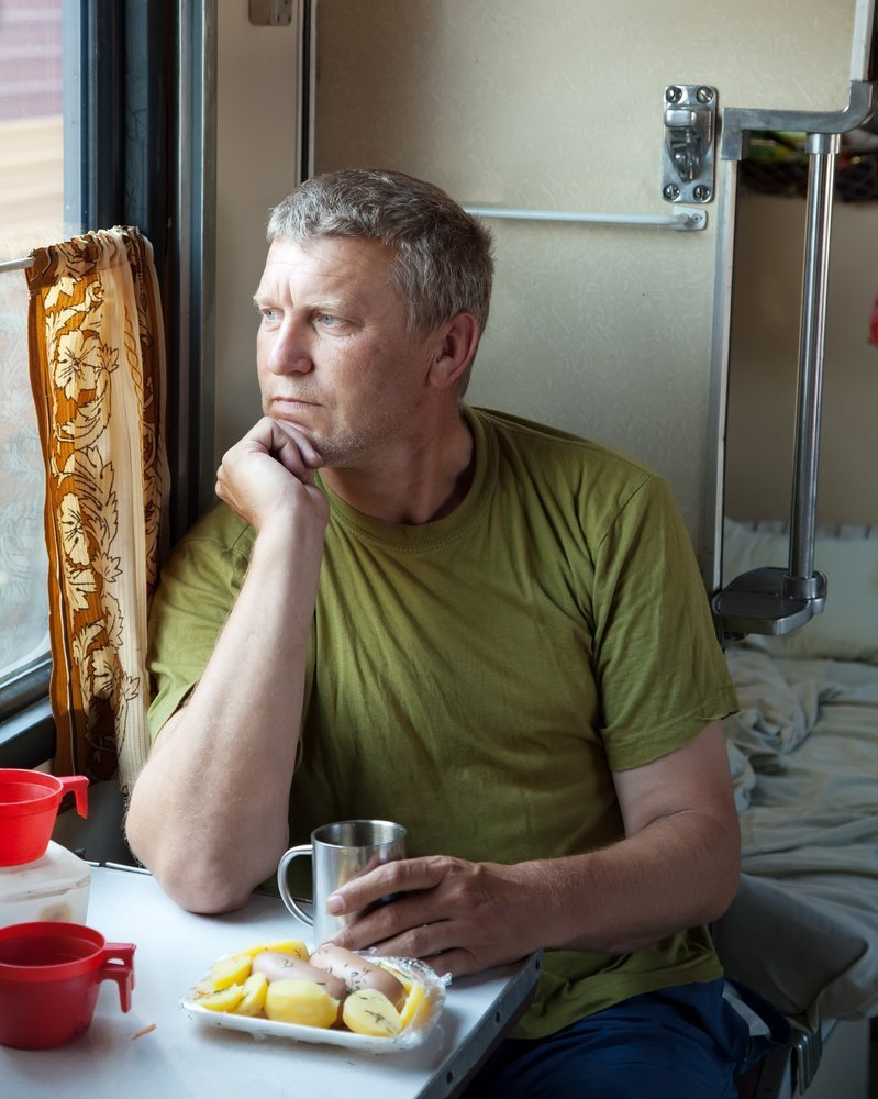 white boomer man looking out a window debating what to do to pay the bills while his wife is sick