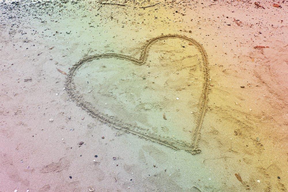 Heart Shape on the rainbow colorful sandy beach for lover concept.