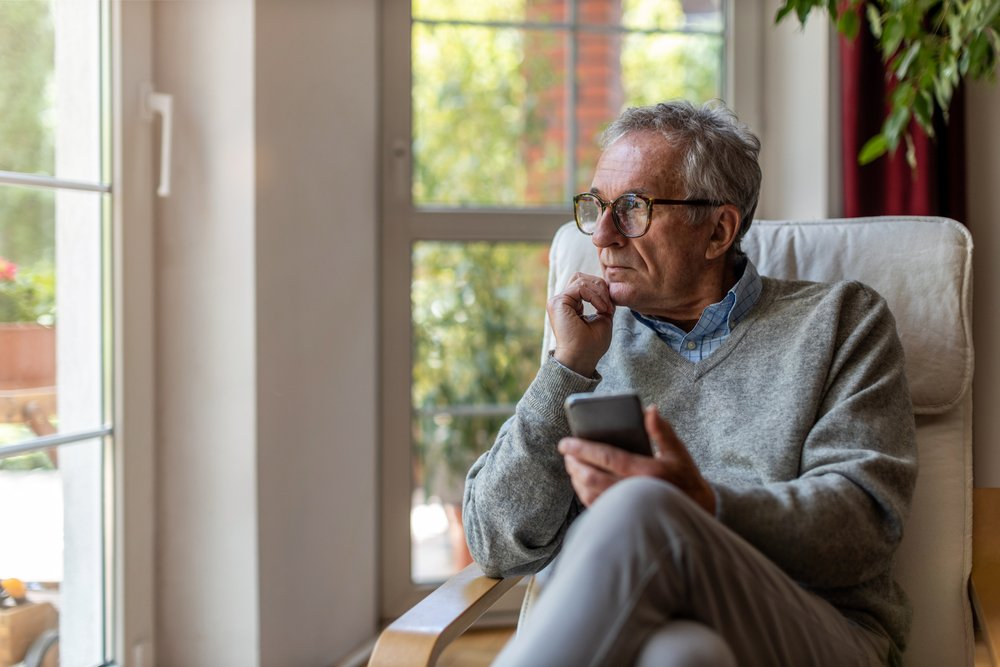 senior man holds a smartphone in his hand while looking out a window contemplatively. thinking about how to respond to a worrying social media post