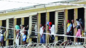 Rioting inmates of the the Camp Street Prison, look out the prison windows in Georgetown, Guyana,