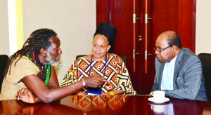Minister of Tourism Edmund Bartlett (right) meets with Edi Wray, of the Rastafari indigenous village after addressing Canex Jamaica, the island's first Cannabiscentred conference on the business potential of the marijuana trade. listening attentively is Mitzie Williams