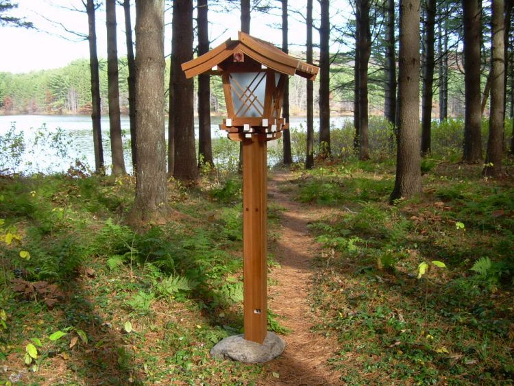 Shrine lantern designed and built by Chris Hall temporarily set up on path near a lake with trees in background
