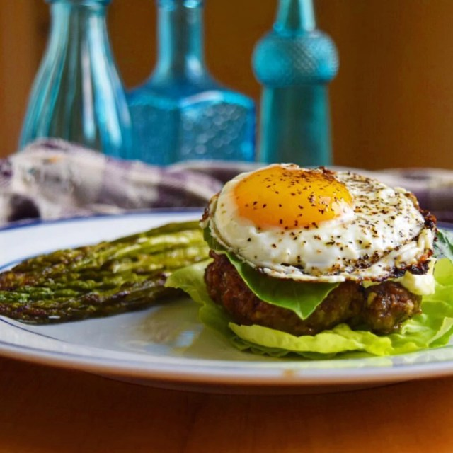fried egg on a burger with asparagus and blue bottles in the background