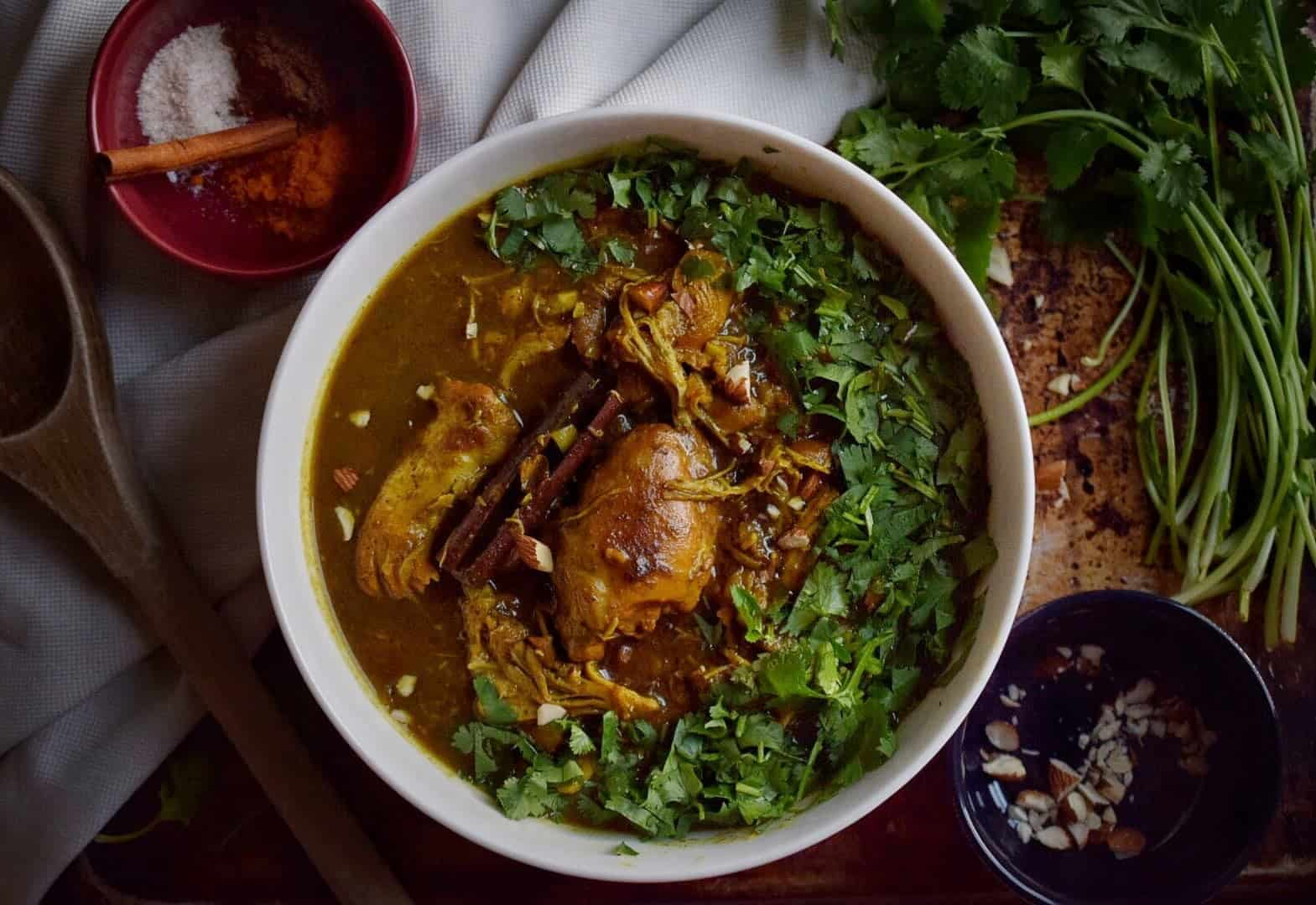 bowl of indian butter chicken surrounded by greens