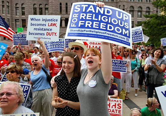 Catholics Caitlin Heaney, right (holding sign), and her sister, Elizabeth, show their support during a rally for religious freedom in downtown Minneapolis June 8, 2012. Dave Hrbacek / The Catholic Spirit