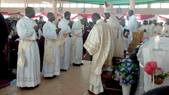 Deacons Kevin Abakisi, Robert Abotzabire, Albert Wugaa and Peter Akudugu stand before Bishop Alfred Agyenta of the Diocese of Navrongo-Bolgatanga during their ordination to the priesthood Dec. 1 in Bawku, Ghana. The four men studied at the St. Paul Seminary.