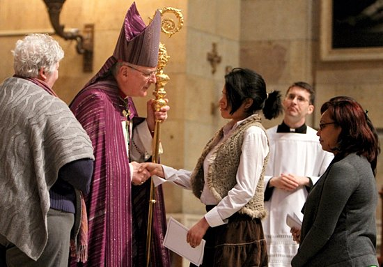 """Catechumen Jacqueline Aleman, who is going through RCIA at St. Mark in St. Paul, greets Archbishop John Nienstedt during The Rite of Election and The Call to Continuing Conversion at the Cathedral of St. Paul Feb. 17. At left is Elisa Cady, RCIA director at St. Mark, and at right is Beatriz Panameno, one of Aleman's sponsors. The rite marks the beginning of the final preparation of catechumens (those not baptized) for the sacraments of initiation, typically celebrated at the Easter Vigil. From the time of the Rite of Election until the time of their initiation, the catechumens are referred to as """"members of the elect."""" During the Call to Continuing Conversion, individuals who already are baptized and who are preparing for entrance into the Catholic Church are recognized. (Dave Hrbacek/The Catholic Spirit)"""