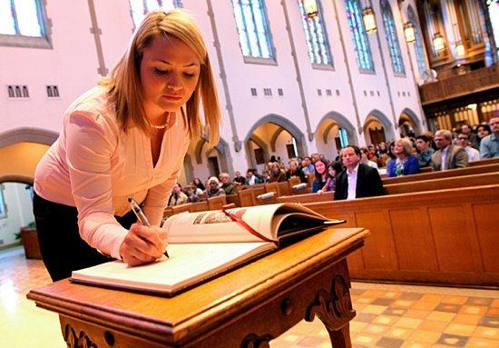 Catechumen Heather Kasel signs the Book of the Elect at Nativity of Our Lord in St. Paul Feb. 17. Kasel went to The Rite of Election and The Call to Continuing Conversion at the Cathedral of St. Paul that afternoon. As of Feb. 12, 214 catechumens and 473 candidates were preparing for initiation. (Dave Hrbacek/The Catholic Spirit)