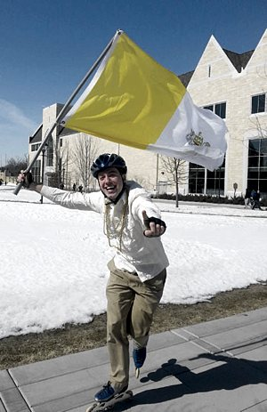 "Junior seminarian Nathaniel  Binversie celebrates in the Lower Quad at the sign of white smoke, yelling to others ""We have a pope!"" Binversie waved the Vatican flag while roller blading through the middle of campus. Caroline Rode / TommieMedia"