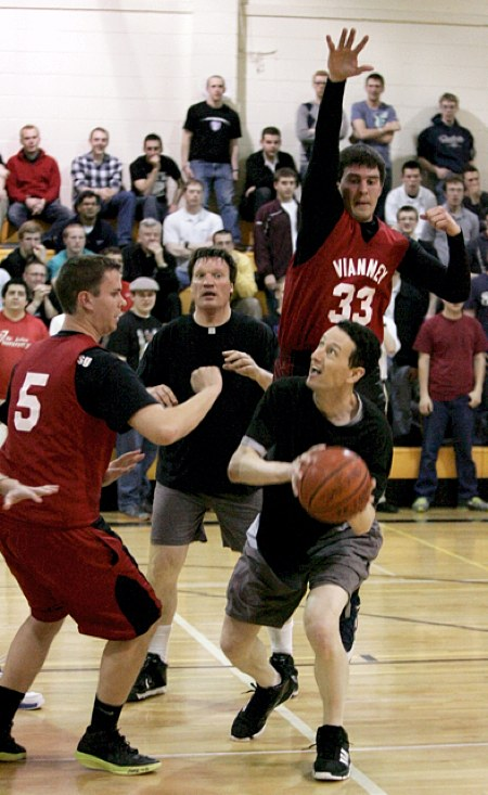 Father Patrick Barnes is surrounded by SJV players as he tries to take a shot. Father Barnes and the team of priests lost to SJV 39-33. (Dave Hrbacek/The Catholic Spirit)