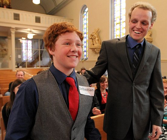 Zach Sobiech, right, of St. Michael in Stillwater, offers a gesture of congratulations to Matt Brown during Brown's confirmation Mass at St. Mary in Stillwater April 22. Sobiech, a friend of the Brown family since his early years, died of cancer May 20 at his home in Lakeland. He was Matt's confirmation sponsor. Dave Hrbacek / The Catholic Spirit