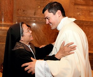 Newly-ordained Father Spencer Howe greets Sister Rose Vu, a member of the Religious of the Good Shepherd, after the ordination Mass. (Dave Hrbacek / The Catholic Spirit)