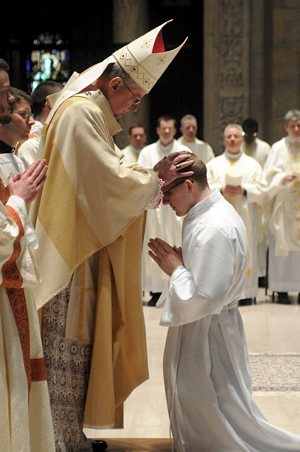 Archbishop Nienstedt ordains  Kevin Manthey with the laying on of hands.