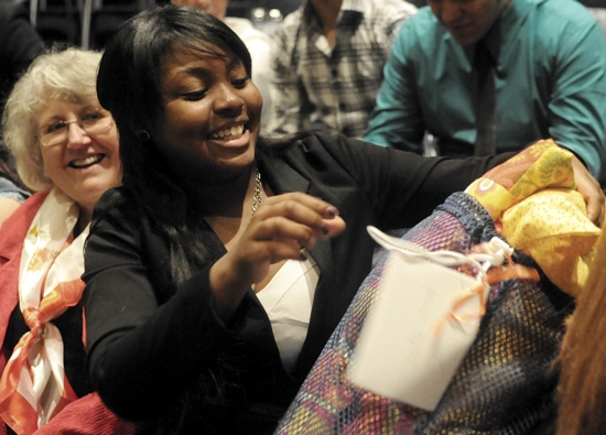 As quilter Winnie White-Scherber watches, Cristo Rey graduate Jasmyn Taylor reacts to the custom-made quilt she received June 7 from the quilting group at Pax Christi in Eden Prairie. The group worked during the school year to make quilts for all 47 graduating seniors. Dianne Towalski / The Catholic Spirit