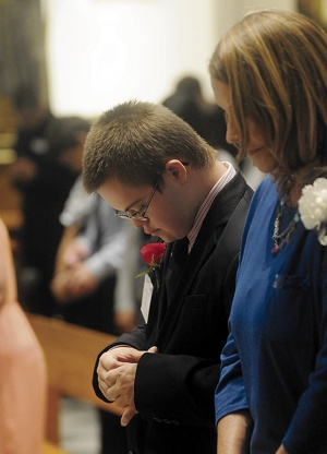 Robert Ginther, 16,  a member of Risen Savior in Burnsville, bows his head during the final blessing.