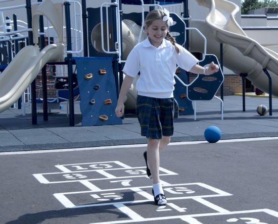 Fourth-grader Alexa Wilgenbusch plays hopscotch on the new parking lot at St. John the Baptist School in Savage. Parish administrators saved more than $20,000 on the new surface by taking advantage of a strategic purchasing program sponsored by the archdiocese. Photo submitted