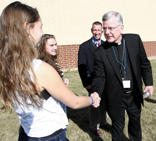 Ally Dudley, left, of St. Patrick in Oak Grove greets Archbishop John Nienstedt during Archdiocesan Youth Day Sept. 21 at Holy Family High School in Victoria. With her is Mady Banken, second from left, also of St. Patrick. Walking with the archbishop is Bill Dill of the Office of Marriage, Family and Life, which sponsored the event.