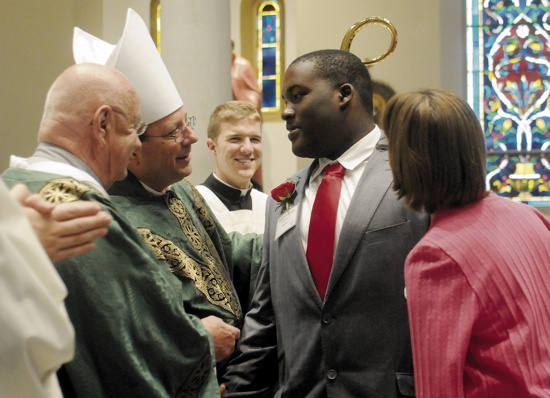Hercules France, 19, a member of St. Alphonsus in Brooklyn Center, shakes hands with Bishop Piché after his confirmation.