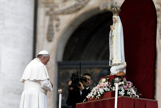 PRAYER TO OUR LADY: Pope Francis prays in front of the original statue of Our Lady of Fatima during a Marian vigil in St. Peter's Square at the Vatican Oct. 12. The statue was brought from Portugal for a weekend of Marian events culminating in Pope Francis entrusting the world to Mary.  CNS photo/Paul Haring