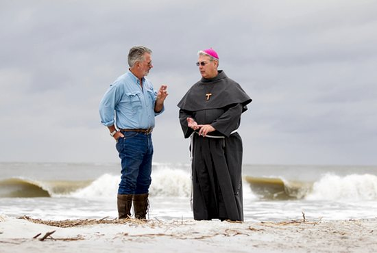 PRESERVING HISTORY: Archaeologist and anthropologist David Hurst Thomas talks with Bishop Gregory Hartmayer of Savannah along the shore of St. Catherines Island in Georgia Oct. 14. Earlier in the day, the bishop celebrated Mass on the site of the island's mission church, which dates back to the 1570s. Scientists on the island continue to excavate with a sense of urgency as erosion from rising sea levels threaten the remains of a vanished American Indian community.  CNS photo/Nancy Phelan Wiechec