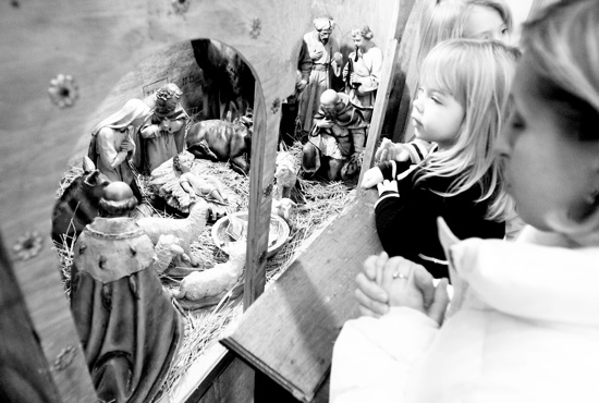 FAMILY PRAYS AT CRECHE ON FEAST OF NATIVITY AT UKRAINIAN CATHOLIC CHURCH