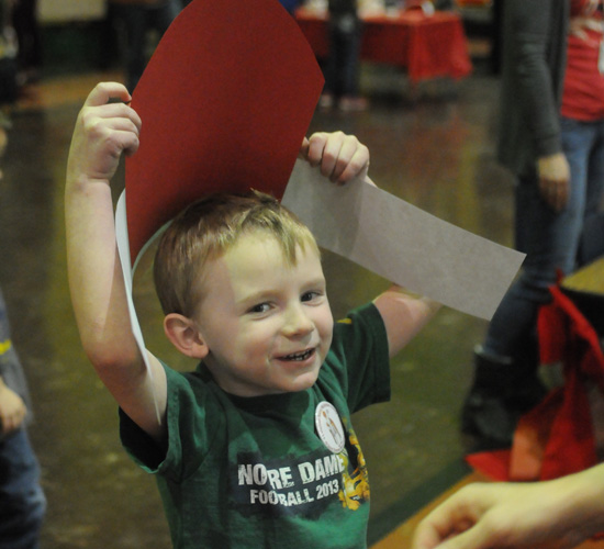 Preschooler Ronan Murphy waited to have the paper miter he made stapled together so he could wear it.