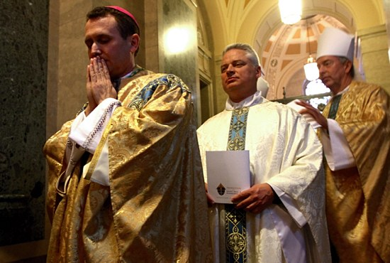 Bishop Andrew Cozzens has a brief prayerful moment before the start of his episcopal ordination Mass Dec. 9 at the Cathedral of St. Paul. Waiting in line with him for the processional are Father Thomas Margevicius, second from left, who assisted Bishop Cozzens during the Mass, and Bishop Peter Christensen of the Diocese of Superior, Wis. Pope Francis appointed Bishop Cozzens as an auxiliary bishop of St. Paul and Minneapolis on Oct. 11.  (Photos by Dave Hrbacek)