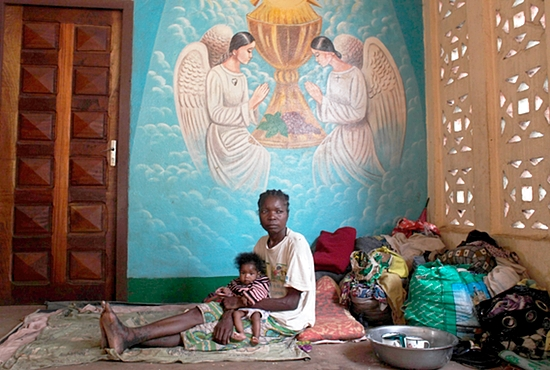 SAFE HAVEN A woman displaced as a result of religious violence holds a child as she rests in a Catholic church in Bossangao, Central African Republic. Dec. 29. French President Francois Hollande has asked the United Nations to play a bigger role in the Central African Republic, its former colony where it has deployed a 1,600-troop peacekeeping mission. CNS photo/Andreea Campeanu, Reuters