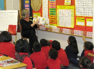 A teacher at Risen Christ School in Minneapolis reads to a class. The K-8 school will transition to full immersion curriculum next fall. Photo courtesy of Risen Christ School