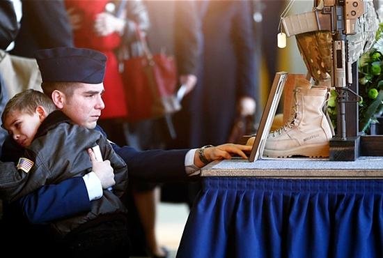 A SAD DAY: Andy Ponce kneels with his son after a memorial service in Lakenheath, England, Jan. 17,  in front of the military gear of his wife, U.S. Air Force Staff Sgt. Afton Ponce, who died in a helicopter accident. The chopper crashed on the eastern coast of England Jan. 7, killing all four crew members. CNS photo/Darren Staples, Reuters