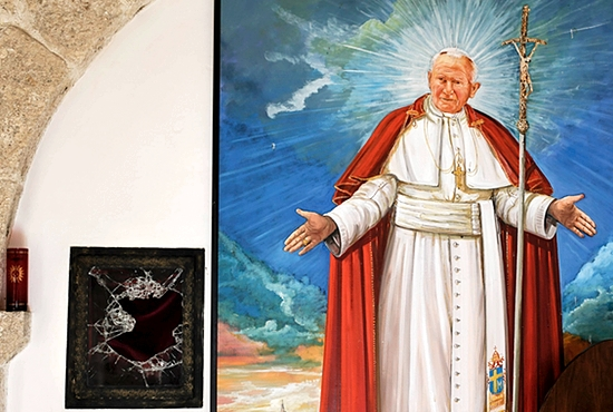 STOLEN RELIC: A broken glass of a niche where the reliquary with the blood of Blessed John Paul II was located is seen next to a painting of the late pontiff in the church of San Pietro della Ienca, near the city of L'Aquila, Italy, Jan. 28. Thieves reportedly stole a relic of the late pontiff from the country chapel 85 miles east of Rome. CNS photo/Max Rossi, Reuters