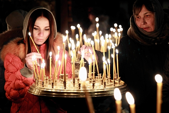 PRAYERS FOR PEACE: Women light candles during a prayer service at a church in Kiev, Ukraine, Feb. 23. Ukraine's acting government issued a warrant Feb. 24 for the arrest of President Viktor Yanukovich, last reportedly seen in the pro-Russian Black Sea peninsula of Crimea, accusing him of mass crimes against protesters who stood up for months against his rule. CNS photo/David Mdzinarishvili, Reuters