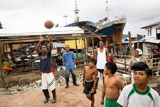 Residents of Tacloban, Philippines, play basketball Feb. 4 amid rubble and two maritime ships that washed ashore during November's Typhoon Haiyan. According to the Philippine government, more than 6,000 people died as a result of Typhoon Haiyan.  CNS photo/Tyler Orsburn