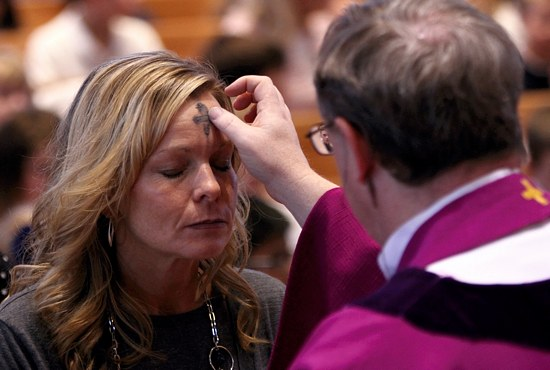 ASH WEDNESDAY Martha Johnson receives ashes on her forehead from Father Thomas Wilson, pastor of All Saints in Lakeville, during an Ash Wednesday liturgy for students of All Saints School. Johnson is a sixth-grade teacher and school librarian. Dave Hrbacek / The Catholic Spirit