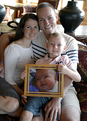 Marc and Mandy Seymour and their son Camden with a picture of Quinn. Photo by Jim Bovin
