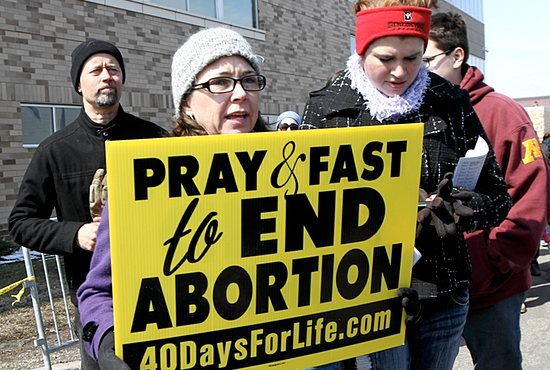 VIGIL FOR LIFE Desiree Schlangen, center, of St. Patrick in Oak Grove carries a sign during the annual Good Friday prayer service for life in front of Planned Parenthood in St. Paul April 18. Next to her at right is Amy Rhein, also of St. Patrick. At far left and behind Schlangen is her husband Mark. Hundreds of people throughout the day came to pray and march in front of the abortion facility. Archbishop John Nienstedt came in the morning to lead and join others in prayer. Dave Hrbacek/The Catholic Spirit