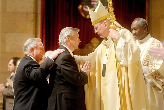 """Candidate David Johnson, center, receives the sacrament of confirmation from Archbishop John Nienstedt during the Easter Vigil Mass April 19 at the Cathedral of St. Paul. At left is Johnson's sponsor, David Hueller. There were seven candidates — those who have been baptized and are seeking full communion with the Church — from the Cathedral parish and six from the University of St. Thomas. During the Mass, the archbishop baptized four elect from the Cathedral parish and two from the University of St. Thomas. Archbishop Nienstedt said during his homily, """"The message of this Easter night is one of great hope. Hope for the catechumen and the candidate. Hope for the sinner. Hope for the archbishop, the priest, the deacon, the religious, the laity. Hope, indeed, for the world. For he is risen, and we have become ambassadors of this great message."""" Dianne Towalski /The Catholic Spirit"""