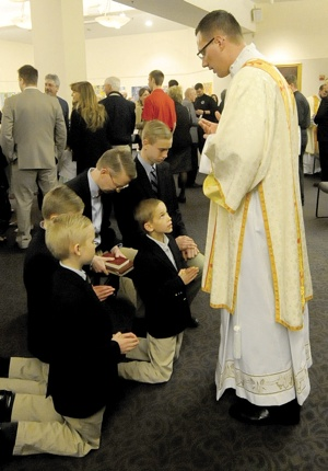 After the ordination Mass, Deacon Jake Anderson blesses Dr. Christian Washburn and his sons, Thomas, 17; Petrus, 12; Aloisius, 11; and Ambrose 9. The Washburns are members of St. Agnes parish in St. Paul.