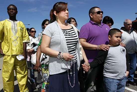 Pilar Monrroy, left, of St. Francis de Sales in St. Paul, prays the rosary with Ivan Solis and his son, Jonathan, also of St. Francis de Sales. Ivan Solis is Monrroy's nephew. Dave Hrbacek/The Catholic Spirit
