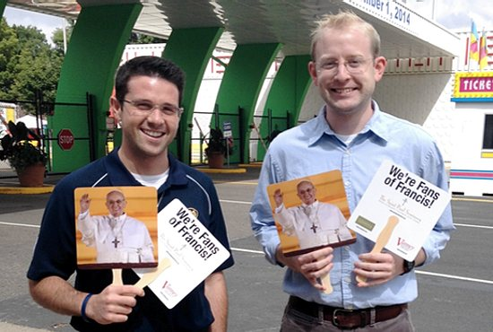 "POPE ON A STICK For the second year in a row, Pope Francis was at the great Minnesota get-together. On Aug. 24, faculty and staff of The Saint Paul Seminary School of Divinity handed out ""Fans of Francis"" at the University of St. Thomas booth at the Minnesota State Fair. Pictured are seminarians Michael Daly, left, and Mark Pavlak. Photo courtesy of Karen Laird/The Saint Paul Seminary"
