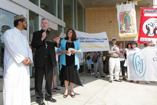 Archbishop John Nienstedt, second from left, joins with other faith leaders at the Faith Action Vigil for Children and Families at the Border Aug. 3 at the Ramsey County Detention Center in St. Paul. They were there along with community members to call for a humane response to Central American refugee children and families seeking safety in the U.S. Archbishop Nienstedt was one of the featured speakers at the event. Another was Asad Zaman, left, of the Muslim American Society of Minnesota. To the right of Archbishop Nienstedt is Estela Villagran Mancero, director of Latino Ministry for the Archdiocese of St. Paul and Minneapolis. Also present were the Sisters of St. Joseph of Carondelet in St. Paul. Sister Susan Hames was one of the speakers.
