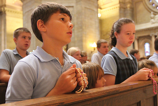 From left, eighth-grader Joe Stokman, kindergartner Emily Kunkel and eighth-grader Mary Grace O'Sullivan of St. Timothy School in Maple Lake participate in the Children's Rosary Pilgrimage at the Cathedral of St. Paul Oct. 7. More than 2,000 children from Catholic schools in the Archdiocese of St. Paul and Minneapolis came for the event, led by Bishop Lee Piché in honor of the feast of Our Lady of the Rosary. Dave Hrbacek/The Catholic Spirit